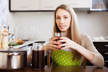 Woman drinking fresh quass from glass