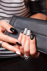 Portrait of manicured nails with nail polish holding a wallet