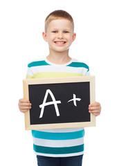 smiling little boy with blank blackboard