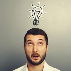 man looking up at drawing light bulb