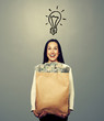 woman with light bulb and money