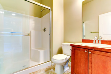 Simple bathroom interior with vanity cabinet and glass door show