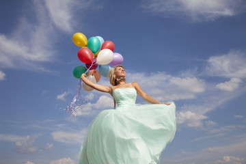 Beautiful, happy woman dancing with balloons