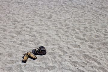 His and hers flip flop sandals on the sandy beach