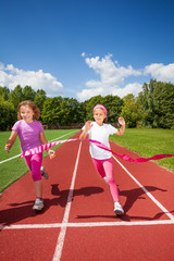 Running girls try reaching the ribbon excited