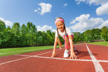 Smiling girl in position on knee ready to run