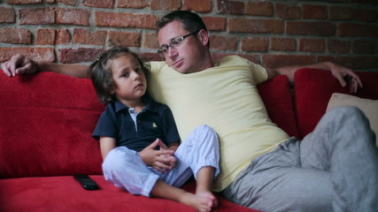 Father and son watching television and enjoying time together