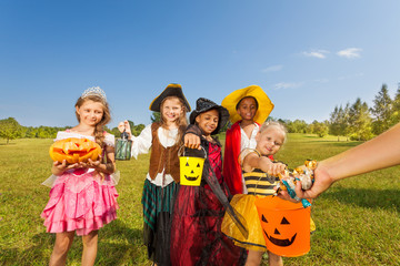 Children in costumes look at hand with sweets