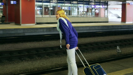 Girl walking with suitcase on platform and waiting for train