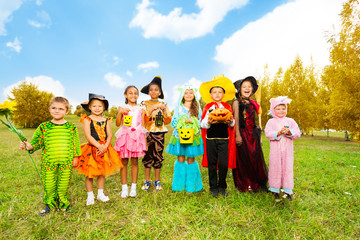 Kids with Halloween costumes stand in row