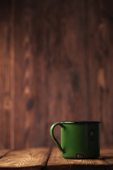 vintage green  enamel mug on old wood