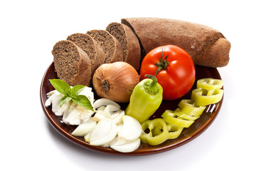 bread and fresh vegetables on the plate isolated on wooden back