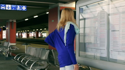 Girl walking with suitcase and checking board on platform