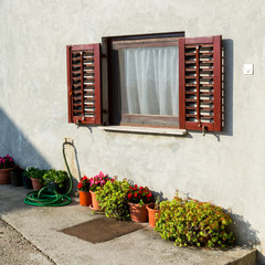 Old traditional window with open wooden shutters and flowers