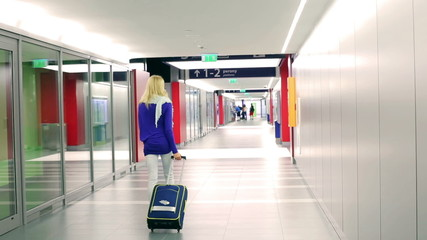 Girl walking back on corridor and pulling luggage