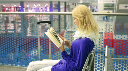 Young woman reading interesting book and sitting on the station