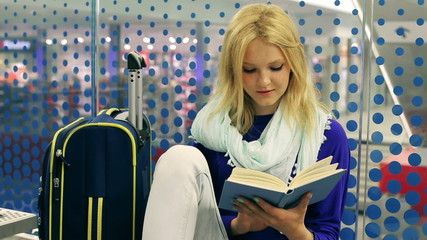 Young woman reading absorbing book on the station
