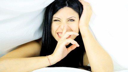 Woman under sheets smiling making silence sign
