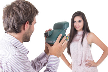 Handsome young man taking photos of beautiful girl with instant