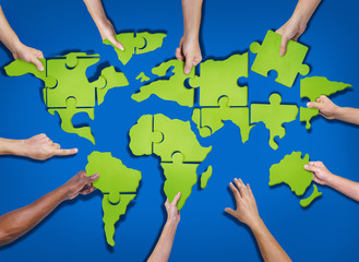 Aerial View of People Forming World Map with Jigsaw Puzzle