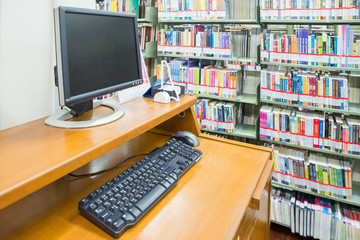 computer in a library with many books and shelves in the backgro