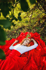 woman in red skirt lying under the tree
