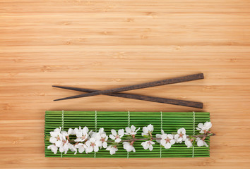 Chopsticks and sakura branch over bamboo mat