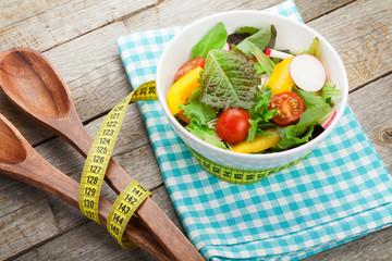 Fresh healthy salad and kitchen utensil