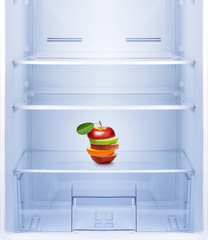 Apples and orange fruit in empty refrigerator.