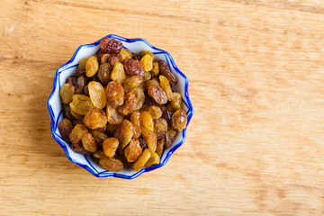 Diet healthy food. Raisin in bowl on wooden background