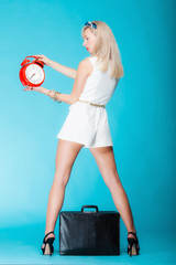 Woman with suitcase red clock. Travel time management concept.