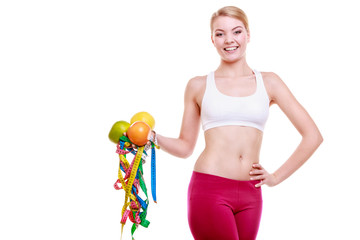 sporty fit woman with measure tapes fruits.