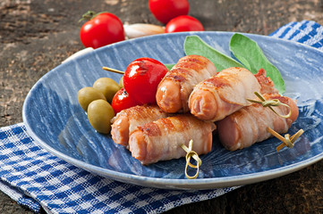 Grilled sausages wrapped in strips of bacon with tomatoes