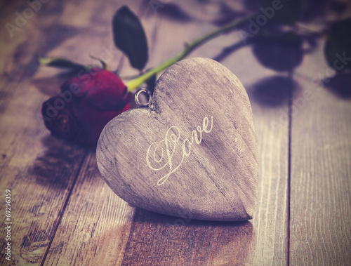 Vintage picture of heart on a wooden background with red rose. V