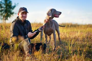 man with weimaraner dog