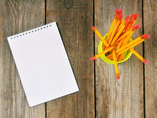 Notebook and pencils on wooden background.
