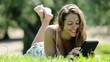 girl lying on grass in meadow enjoying and reading  ereader