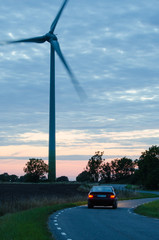 Car drives at a winding road with a wind turbine at roadside