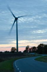 Wind turbine at winding road in a rural landscape