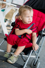 toddler boy sitting in the red stroller