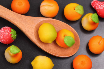 Marzipan fruit shapes in a wooden spoon