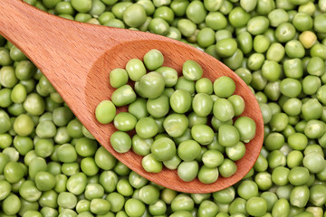 Fresh green peas in a wooden spoon