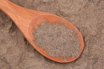 Ground black pepper in a wooden spoon