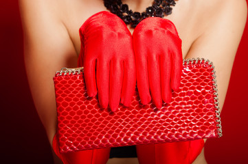 Female hands in red gloves holding a red clutch bag