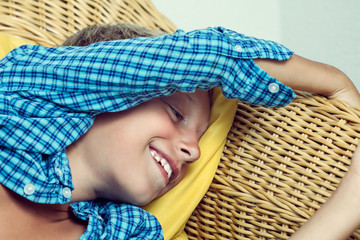 Beautiful funny child lying on wicker sofa laughing