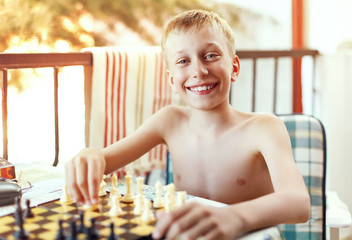 Beautiful boy sitting outdoors in summer playing chess laughing