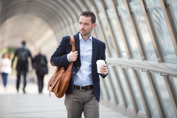 Young attractive man drinking coffee on his way