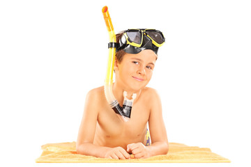 Little boy with a snorkel lying on a towel