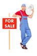 Plumber standing by a for sale sign