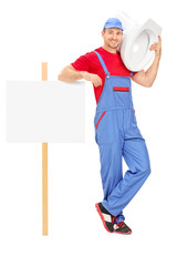 Male plumber standing by a blank signboard